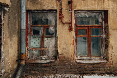 Fotografia  Shabby grungy cracked wall, broken windows, covered buy cloth and polyethylene f
