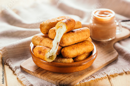Cheese fingers, typical Venezuelan appetizer called tequeños accompanied with a pink sauce on a wooden board
