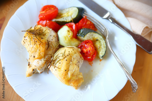 Fotografía  White plate with chicken breast pieces, zucchini, tomatoes and rosemary