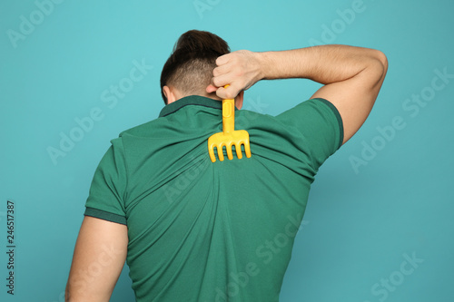 Obraz Young man scratching back with toy rake on color background. Annoying itch - fototapety do salonu
