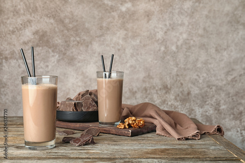 Glasses with healthy protein shake and ingredients on table. Space for text