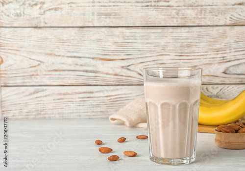 Composition with glass of healthy protein shake on table. Space for text