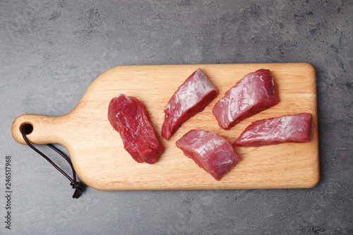 Board with raw meat on grey background, top view