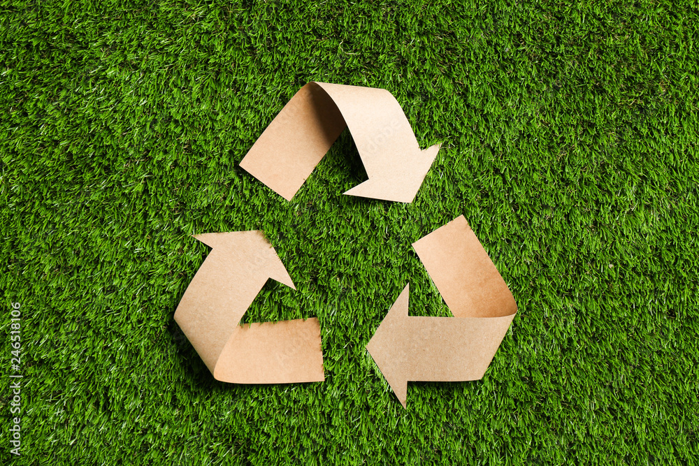 Fototapety, obrazy: Recycling symbol cut out of kraft paper on green grass, top view