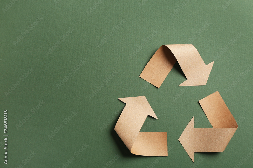 Fototapeta Recycling symbol cut out of kraft paper on green background, top view. Space for text