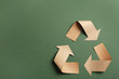 Recycling symbol cut out of kraft paper on green background, top view. Space for text