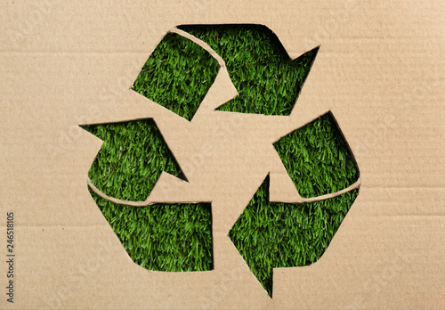 Sheet of cardboard with cutout recycling symbol on green grass, top view