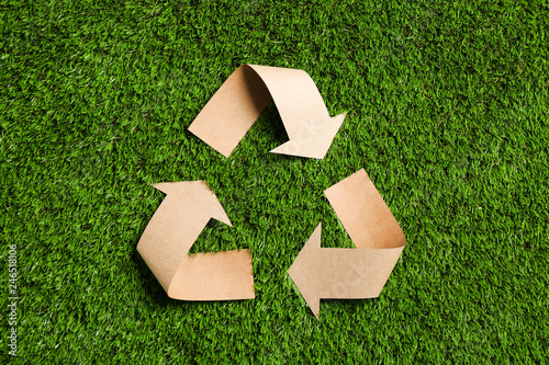 Recycling symbol cut out of kraft paper on green grass, top view