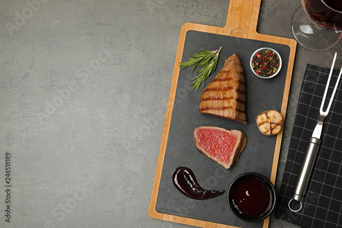 Grilled meat served with sauce and wine on table, flat lay. Space for text