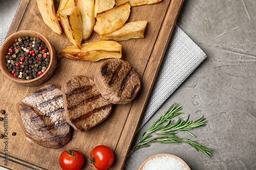 Grilled meat served with garnish on grey background, flat lay. Space for text
