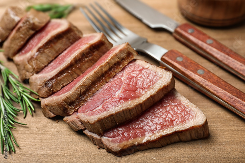 Cut roasted meat with rosemary on wooden background, closeup