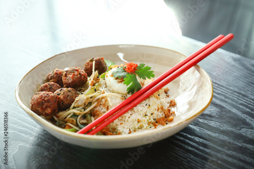 Plate with rice, meat balls and chopsticks served on table