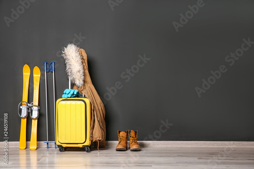 Suitcase, jacket and skis on floor against black wall, space for text. Winter vacation