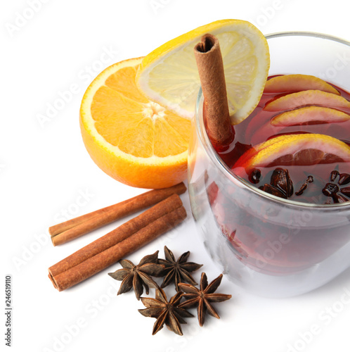 Glass of mulled wine, fresh orange, cinnamon sticks and lemon isolated on white