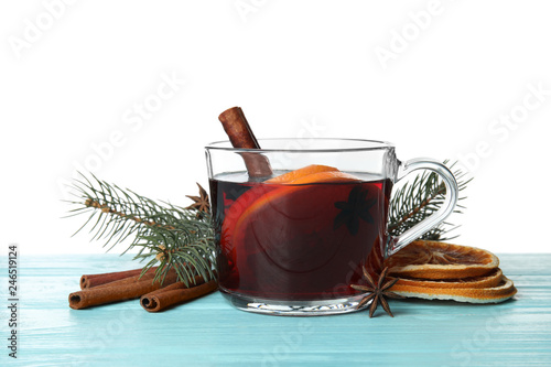 Composition with glass cup of mulled wine, cinnamon, orange and fir branch on table against white background