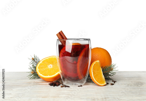Glass of mulled wine with fir branch, cinnamon and orange on table against white background