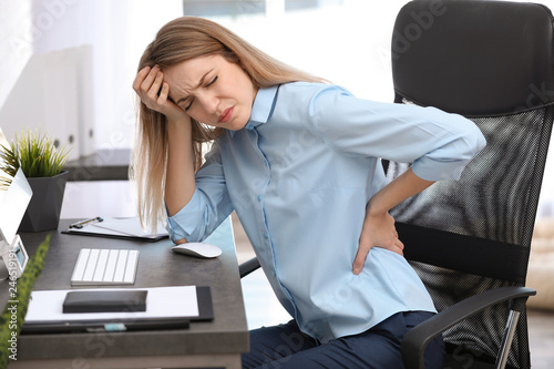 Fotografía  Young woman suffering from back pain in office