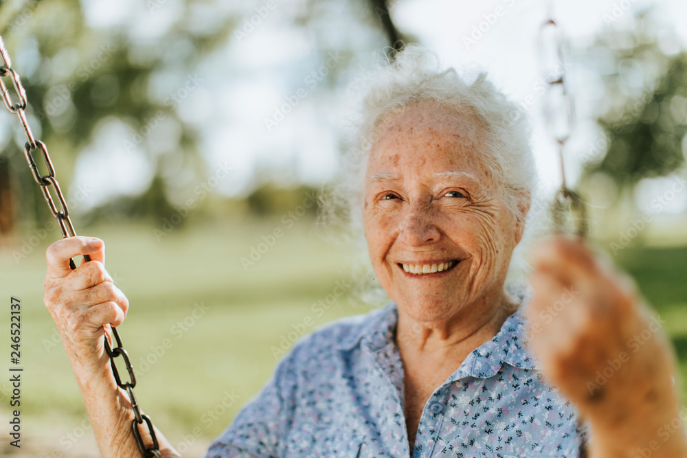Fototapety, obrazy: Cheerful senior woman on a swing at a playground