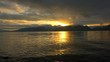 Time lapse of sunset over sea and far away mountains in Tromso, Norway. Clouds move fast over water that reflects orange sky. Small rocks visible in the foreground.