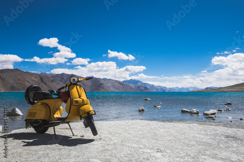 Fotografía Yellow motocycle in front of clear natural water of lake Pangong in Ladakh, Indi