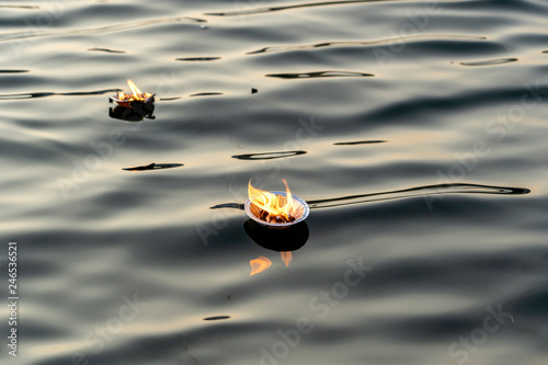 Spoed Fotobehang Asia land Hinduism religious ceremony puja flowers and candle on river Ganges water, India