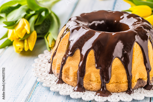 Delicious holiday slovak and czech cake babovka with chocolate glaze. Easter decorations - spring tulips and eggs