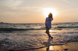 Girl rests and has fun in sea wave at sunset
