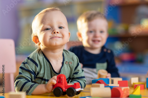 Happy smiling babies kids are playing with educational toys in nursery
