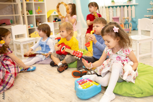 Children learning musical instruments on lesson in kindergarten or daycare - 246552979