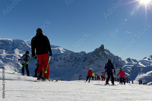 Skiers on beautiful ski slope in Alps, people on winter holidays. Winter mountain landscape