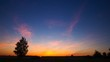 4k timelaspe of twilight over fields and birch tree silhouette.