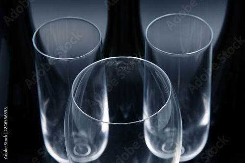 Three empty wine bottles and three empty wine glasses