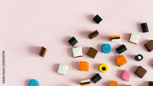 Photo Liquorice Allsorts Sweets on pink background. Copy space