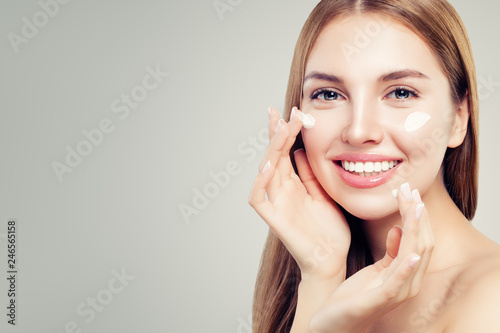 Fotografía Exited beautiful woman with healthy clear skin applying moisturizing cream on her face, closeup portrait