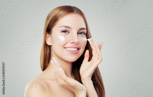Happy young woman applying cream on her face Wallpaper Mural