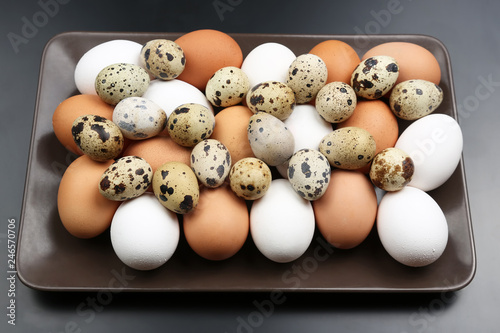 different quail and chicken eggs lie together on a plate