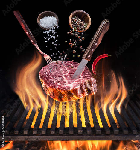 Raw Steak cooking. Conceptual picture. Steak with spices and cutlery under burning grill grate.