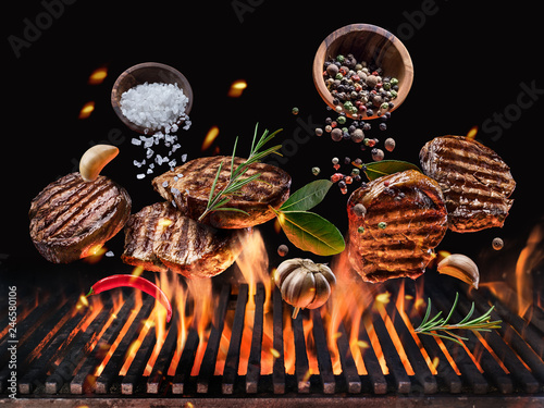 Obraz na plátne Grilled beef steaks with vegetables and spices fly over the glowing grill barbecue fire
