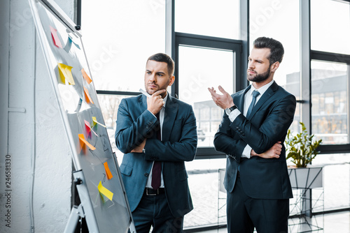 handsome businessmen looking at white board and talking in modern office