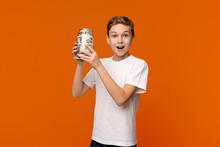 Emotional Boy Holding Glass Money Box On Orange Background