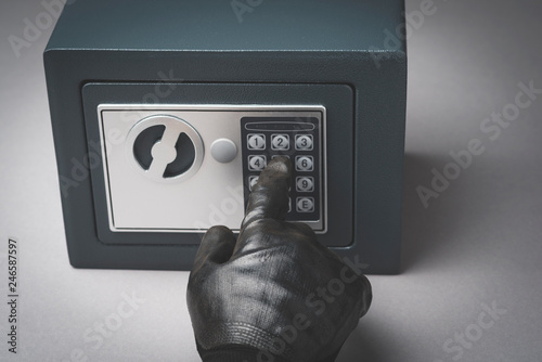 Close-up Of A Thief's Hand Wearing Gloves Unlocking Safe Wallpaper Mural