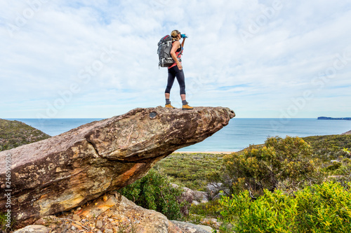 Fotografia  Hiker on rock cliff precipice with views