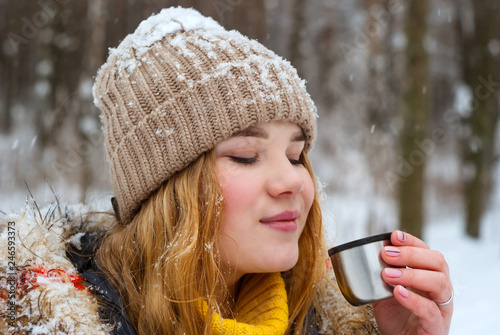 Fotografía  girl blowing on hot tea in winter outdoors