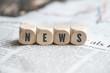 """Leinwandbild Motiv Würfel mit dem Wort """"NEWS"""" auf einer Zeitung"""