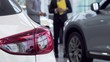 Selective focus on a car, salesman talking to the customer on the background. New automobile on foreground, man choosing new auto at the dealership. Driving concept