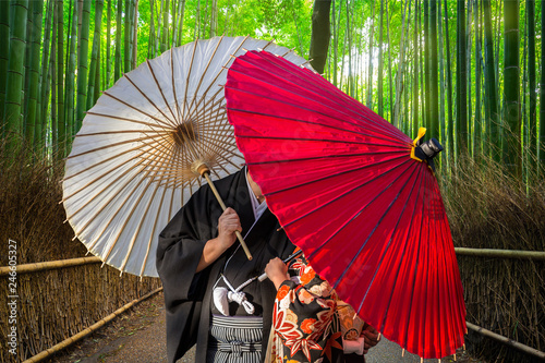 Deurstickers Asia land Couple with traditional japanese umbrellas posing at bamboo forest in Arashiyama