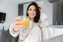 Image Of Attractive Woman 30s Drinking Orange Juice, While Resting In Bright Modern Room