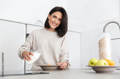 Photo  Image of attractive woman 30s making breakfast with oatmeal and fruits, while st
