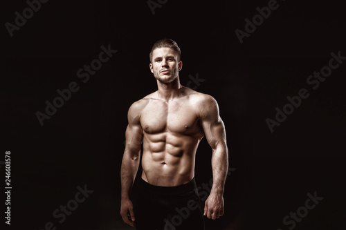 Fotografía Muscular model young man on dark background