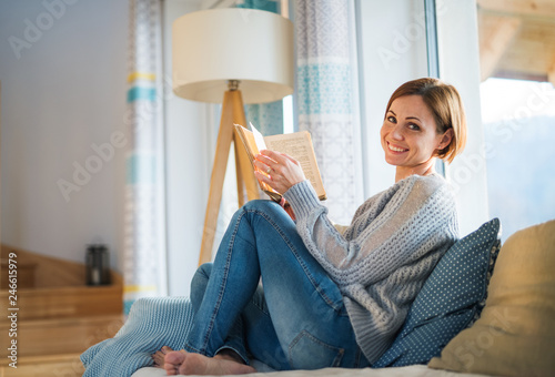 Fotografia A young woman sitting indoors on a sofa at home, reading a book.